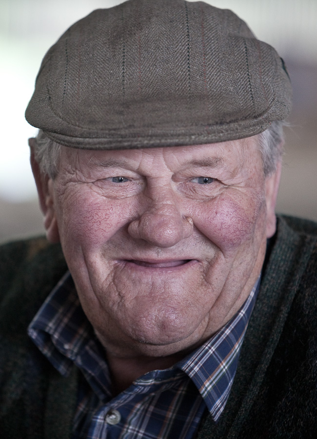 Close head shot of a farmer in a flat cap smiling to someone off-camera.