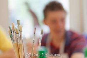Photo focusing on a cluster of paint brushes in a pot with a boy out of focus in the background