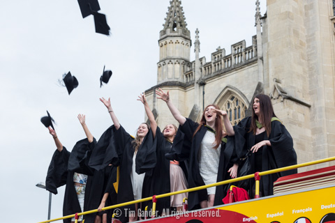 Graduates standing on top of an open-top bus throw their mortar boards in the air