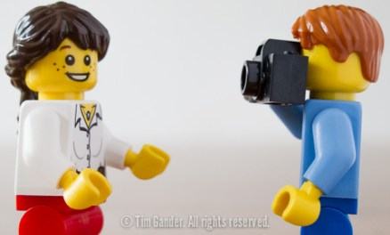 Lego male minifig with camera takes picture of female minifig.