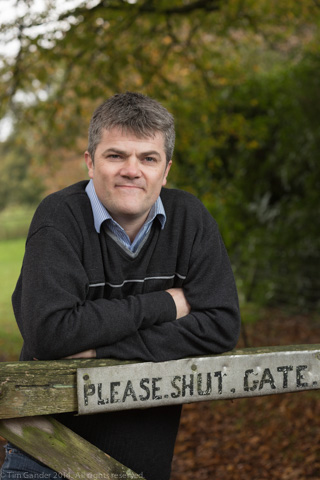 Chef John Melican stands at a farm gate with the sign PLEASE SHUT GATE nailed to it
