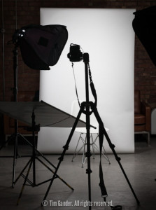 A portrait photography setup with lights, backdrop and camera on a tripod.