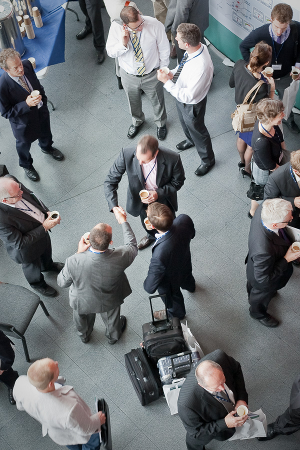 Photo taken from a high viewpoint showing a foyer of businesspeople networking over coffee with two figures shaking hands at the centre of the image.
