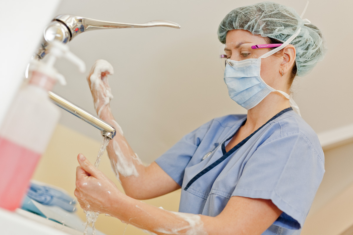 A female dental nurse scrubs in at a sink ready for the next patient.