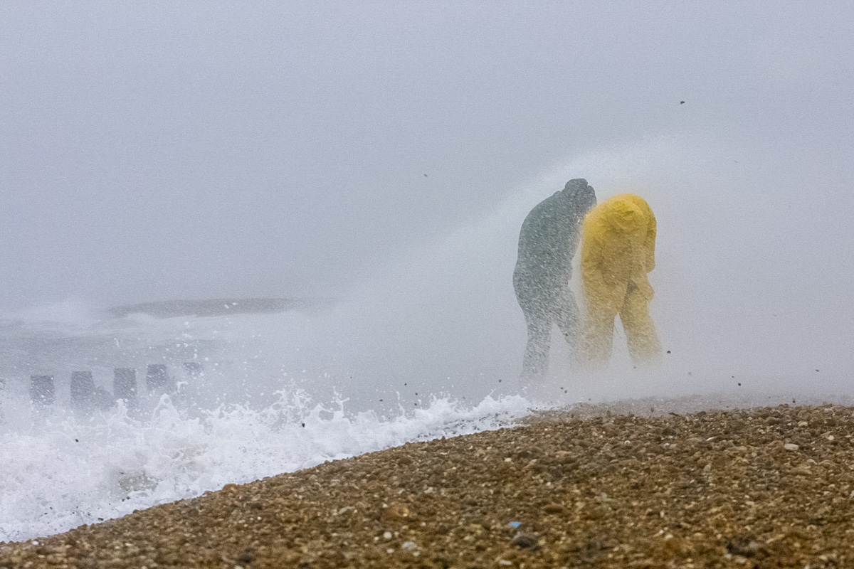 Two men brave the wind, waves and flying pebbles on Hayling Beach.