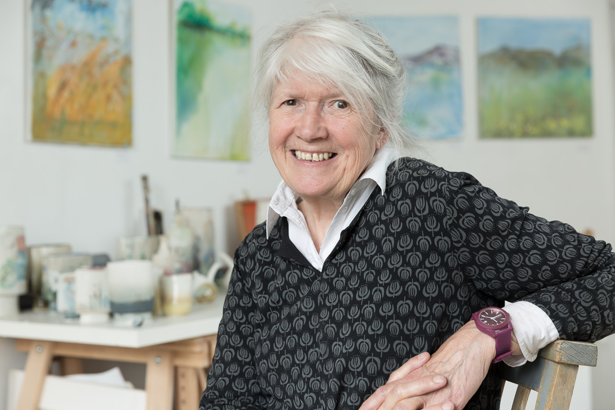 Portrait of Bradford on Avon ceramicist Jane Gibson in her studio, seated and smiling to camera.