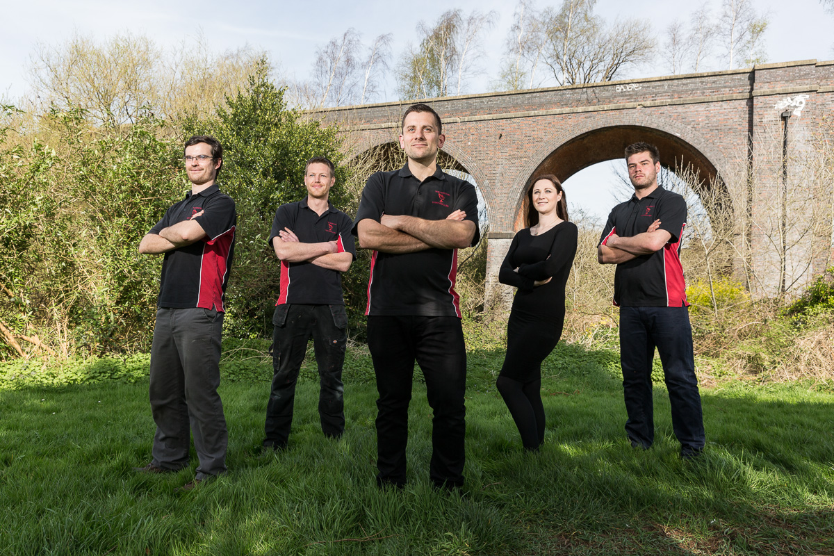 The Bristol Pest Controller team outside in a park in Bristol with a railway viaduct behind.