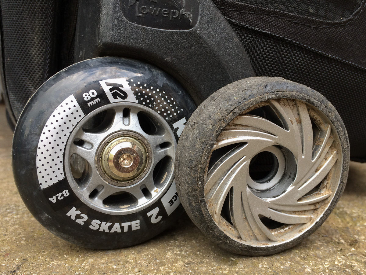 New inline skate wheel fitted to a rolling camera bag with the old wheel standing adjacent for comparison.