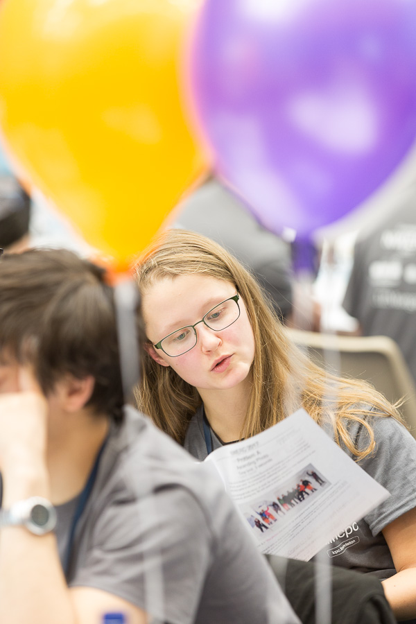 A female student checks over the printed challenge notes, surrounded by balloons and other students which are out of focus.