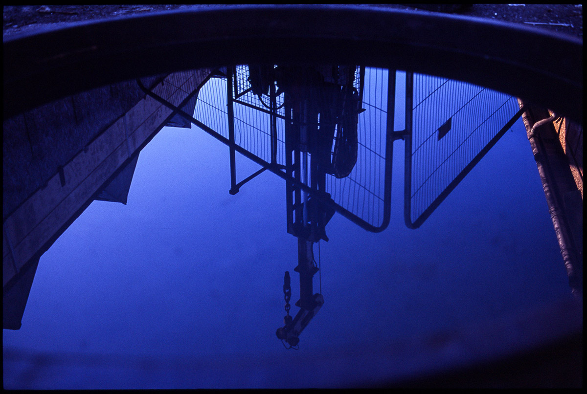 View of a drilling rig reflected in the water used to keep the drilling pipes lubricated.
