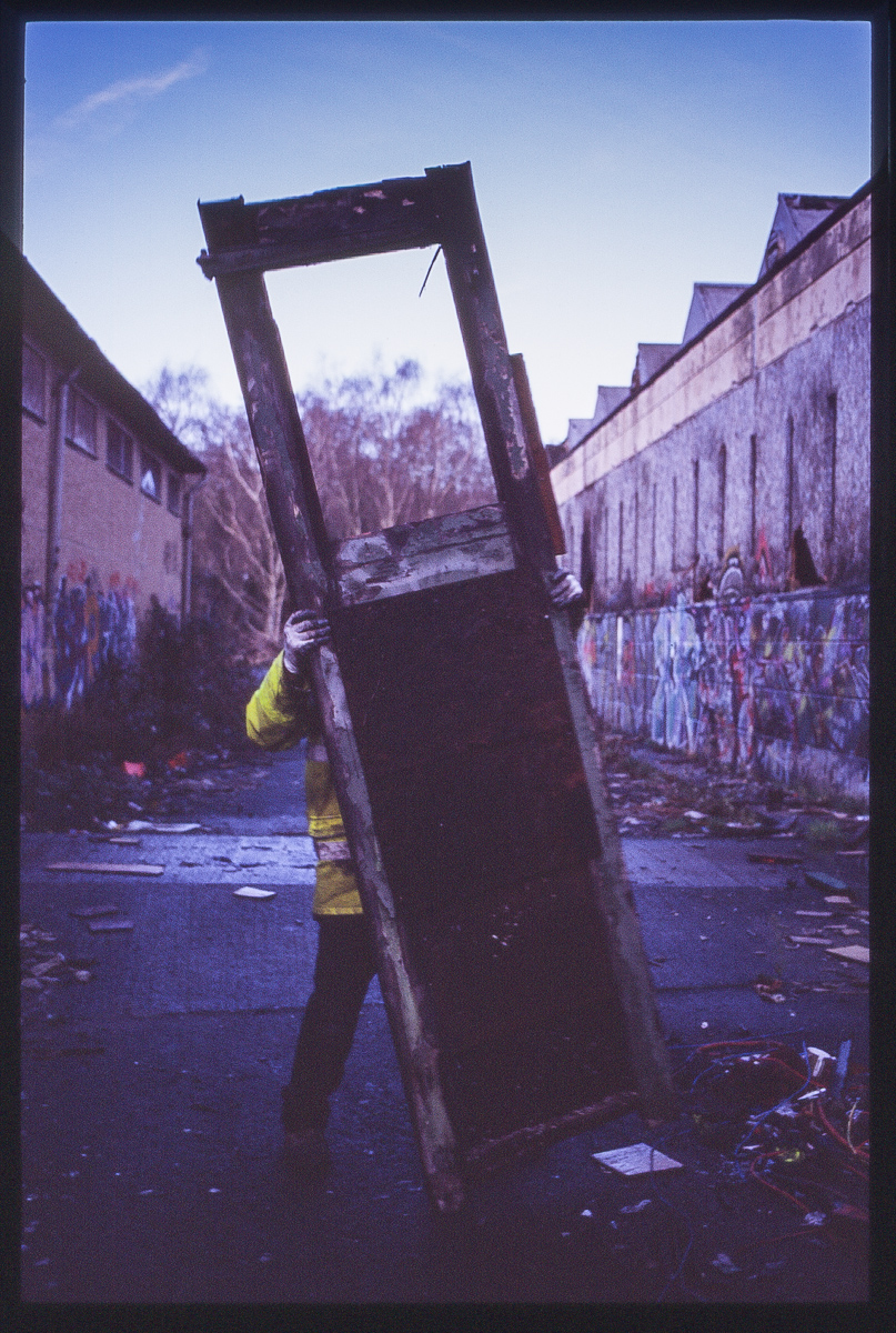 Colour photo of a workman carring a broken door during clean-up. Only his legs, arm and hands are visible as the door obscures the view of the man.