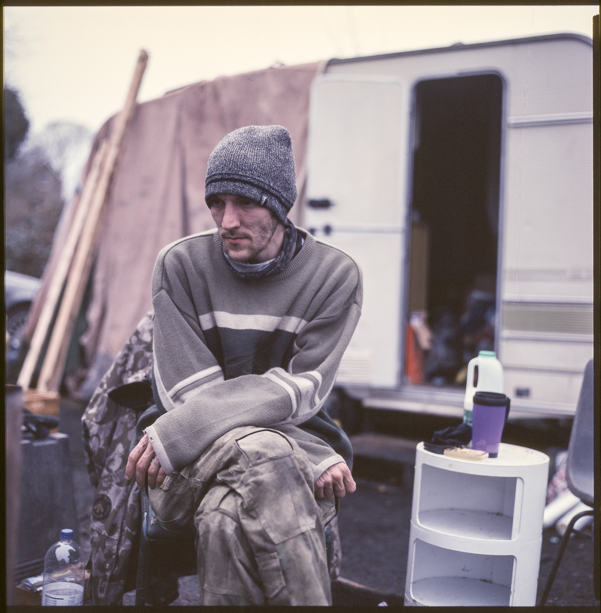 Colour portrait of Dylan, seated and looking down with Alby's caravan behind.