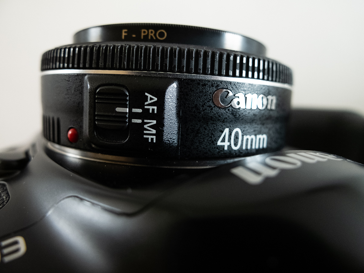 A very close side view of the Can EF 40mm f/2.8 lens showing the Canon logo, lens name and auto focus switch.