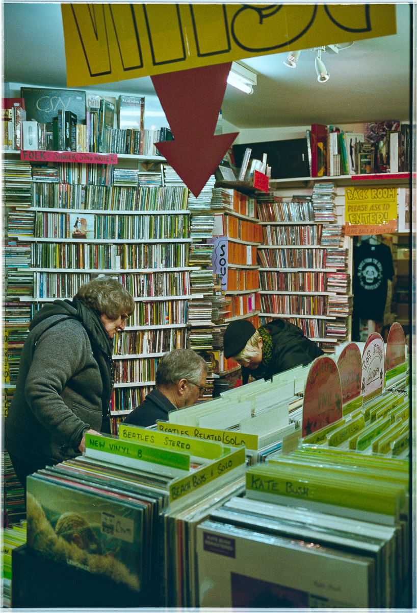 A man and two women look down behind a rack of vinyl records to search in more boxes of records for a birthday gift.