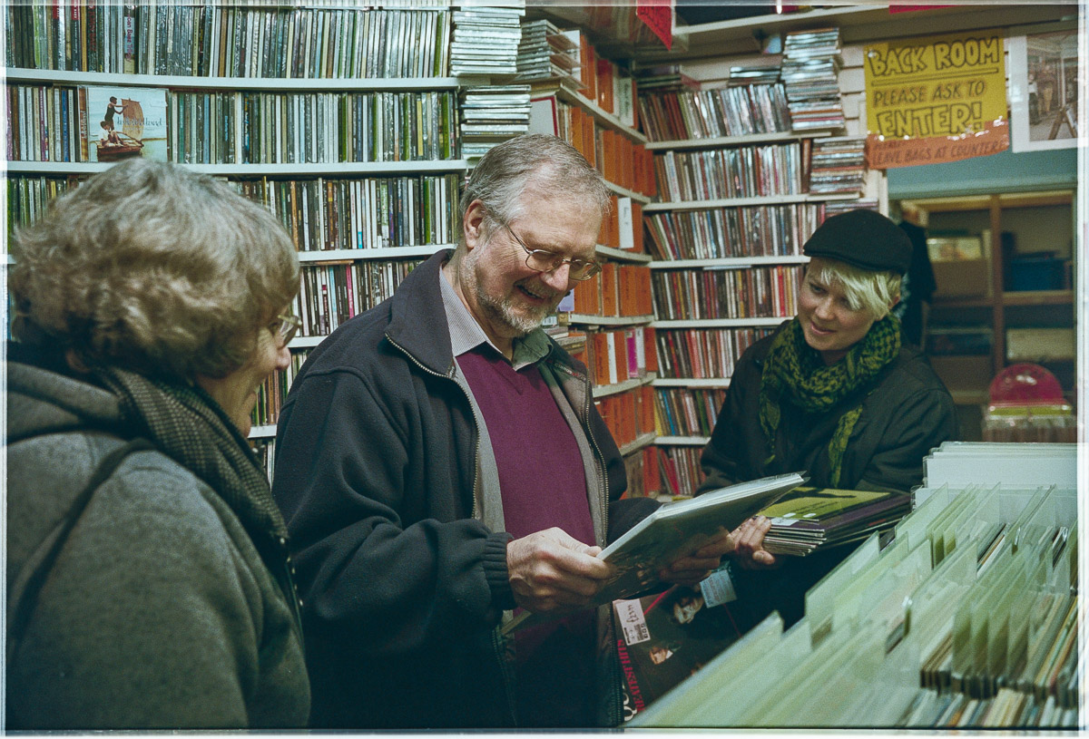 A man smiles, looking down at a vinyl record while his wife and possibly daughter look on.
