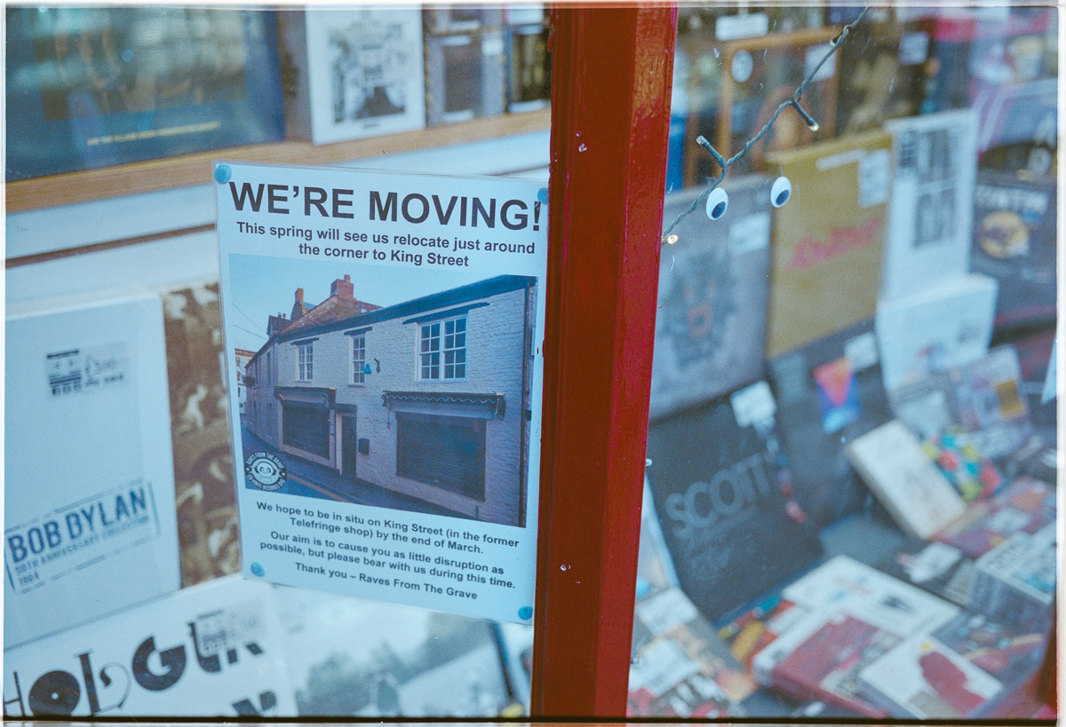 A sign in the shop window announces the date of the move and the new address.