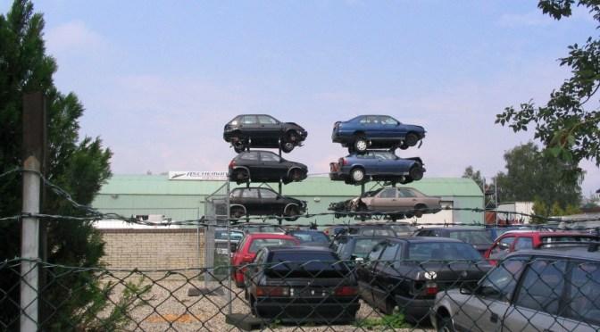 Ein Schrottplatz mit übereinandergestapelten Autos