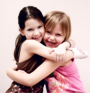 Two happy little girls children hugging and smiling