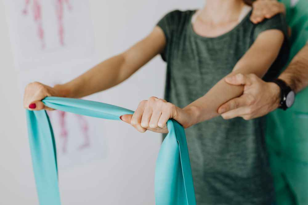 crop anonymous woman stretching elastic band near professional chiropractor