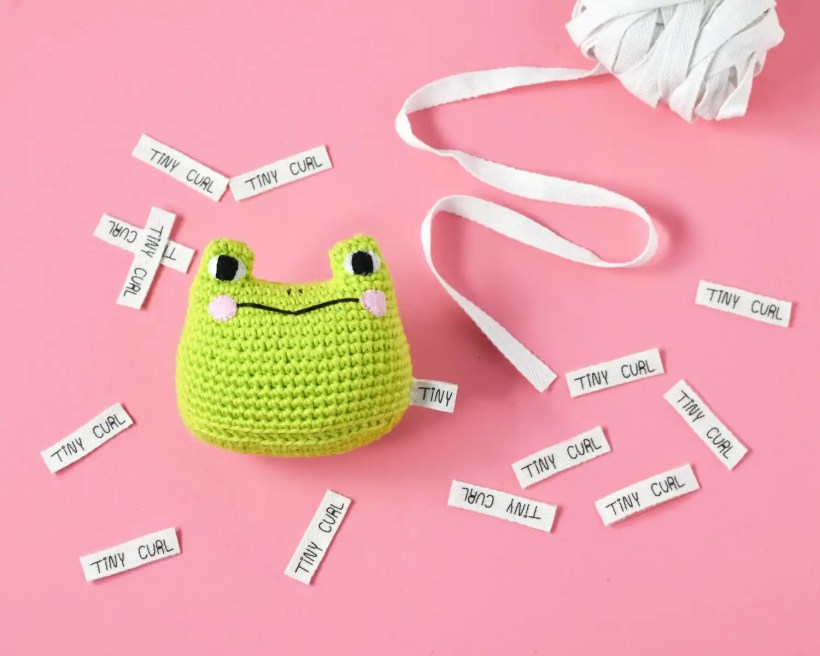 An amigurumi Frog sitting with scattered custom fabric tags made with this how to guide for creating DIY custom fabric tags.