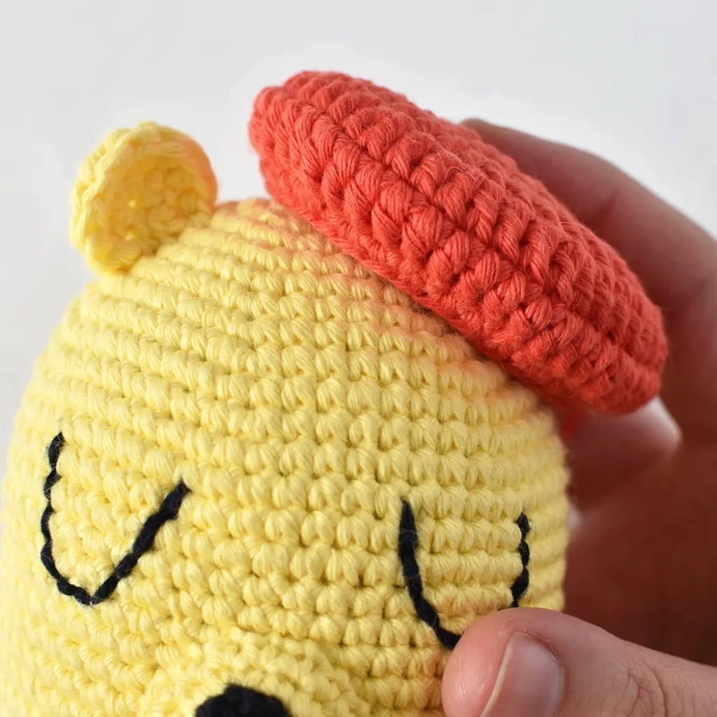 Process pictures for attaching the amigurumi beret to the doll.