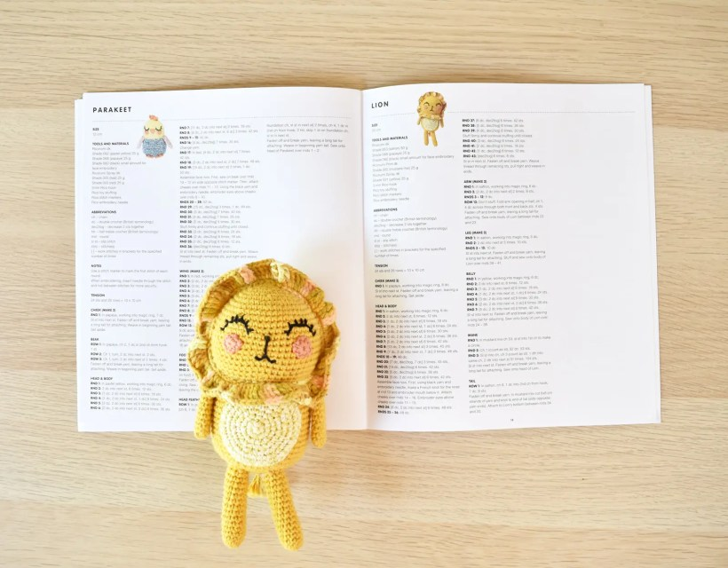 Ricorumi Wild Wild Animals amigurumi book sits on a wooden table and is open to a page showing the parakeet and lion amigurumi patterns and crochet lion is resting on top of the book.