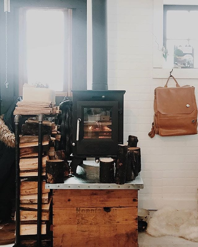 Tiny wood stove, stand, and wood box.