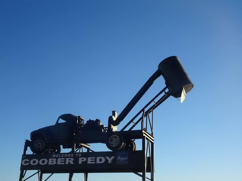 Cartello d'ingresso a Coober Pedy con la macchina per l'estrazione dell'opale