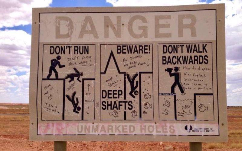 """Segnale di pericolo """"Danger"""" vicino alle buche delle miniere di opale a Coober Pedy, la città sotterranea in South Australia"""