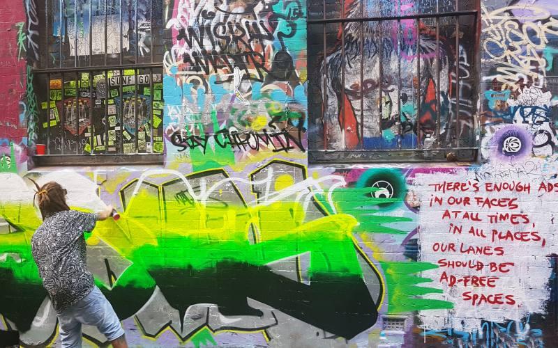 Artista di strada mentre fa un murales a Melbourne