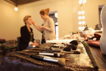 stylist applying make up for bride