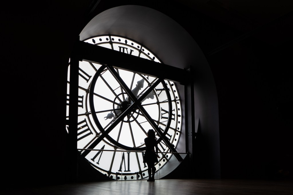 A woman staring through the famous clock at Musee d'Orsay, Paris.