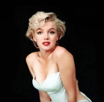Marilyn Monroe mirando a la cámara directamente. Va vestida con un vestido blanco escotado sobre fondo negro.