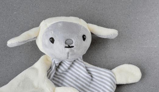 Muñeco de peluche doudou, parece una ovejita.