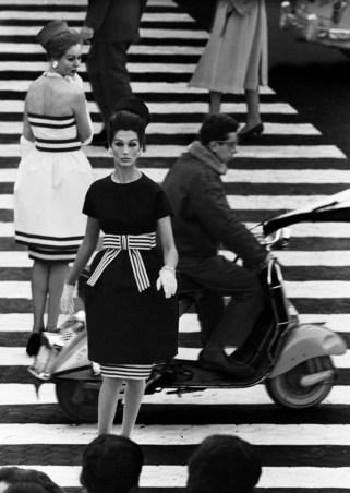 Foto en blanco y negro donde aparecen dos modelos vestidas con un vestido blanco y otro negro, mientras cruzan un paso de zebra