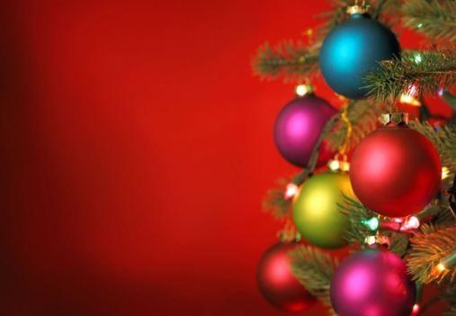 Imagen de adornos de bolas de navidad colgando de unas ramas del árbol de Navidad. Sobre fondo rojo