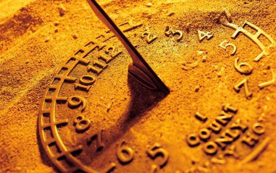 Imagen artística de un reloj solar sobre una superficie de arena.