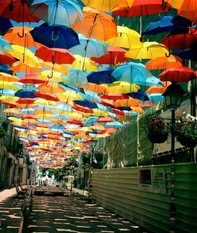 Imagen de una calle con adornos de paraguas de muchos colores en la parte superior a modo de techo.