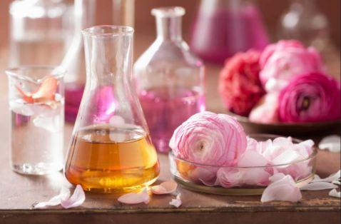 Imagen con botellas transparentes de fragancias, rosas y pétalos de rosas