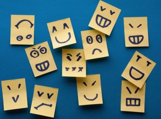 Imagen con varios post-it con diferentes expresiones de emociones dibujadas. Todos los post-it están enganchados en un fondo azul.