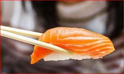 En la imagen se aprecia un nigiri de salmón y arroz cogido entre dos palillos