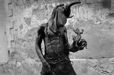 Foto tribal en blanco y negro donde aparece un hombre con la cabeza tapada y encima unos cuernos, mientras sujeta un lagarto con una mano