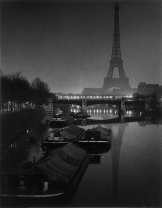 Foto nocturna en blanco y negro donde figura el río Sena con la Torre Eiffel al fondo.