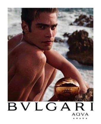 Foto de un modelo en la playa anunciando el perfume de la marca Bvlgari