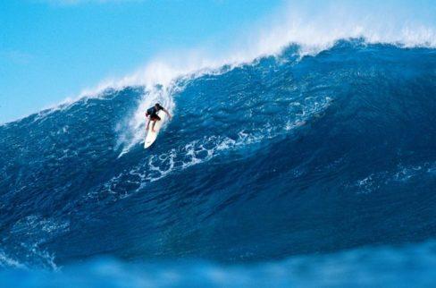 Foto de un hombre haciendo surf sobre unas olas azules gigantescas.