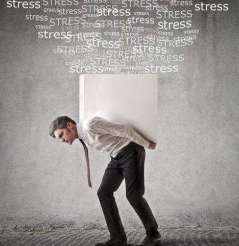 Foto de un hombre ejecutivo con un gran bloque blanco sobre las espaldas y encima muchas palabras de stress