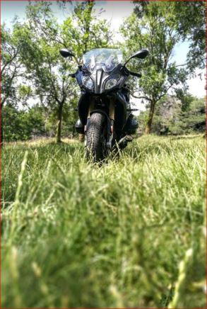 Bonita foto de la R1200 RS tomada de forma frontal pero a ras de suelo en una superficie con hierba