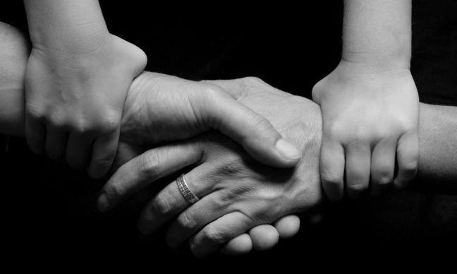 Imagen en blanco y negro donde aparecen cuatro manos unidas en un acuerdo