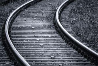 imagen en blanco y negro de un trozo de unas vías de tren en forma de curva