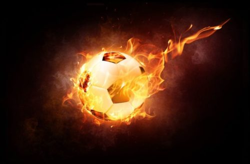 En la foto un balón de fútbol envuelto en llamas de fuego